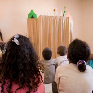 Niños mirando una actuación de títeres